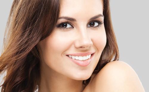Beautiful brunette girl smiling after porcelain veneers by ArtLab Dentistry