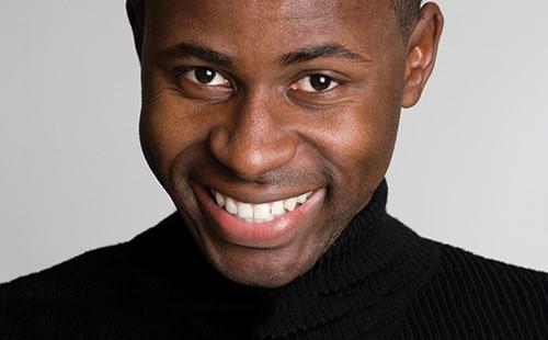 Young man in black turtleneck smiling after dental procedure.